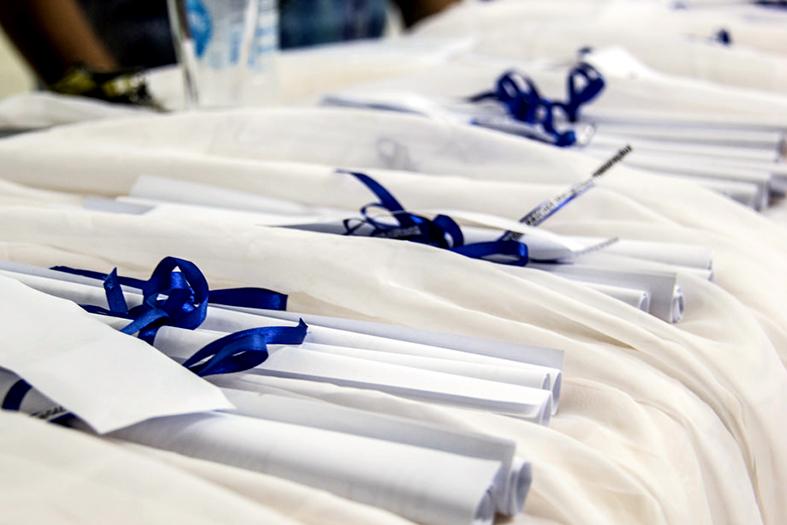 Diplomas enrolado como canudos dispostos sobre mesa com toalha branca.