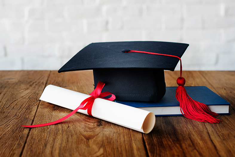 Diploma, chapéu de formando e livro repousam sobre mesa de madeira.