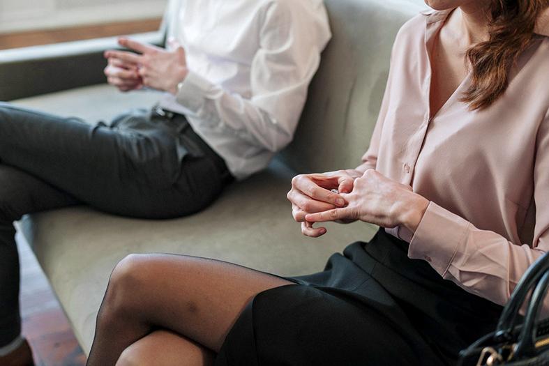 detalhe de um homem e uma mulher de pele branca. Ele está vestindo uma calça jeans e uma camisa de botão na cor branca e ela está de saia preta e uma blusa de botão na cor rosa. Ambos estão retirando as alianças de casamento dos dedos.