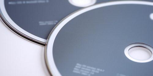 Detalhe de dois discos do tipo DVD com rótulo na cor cinza.
