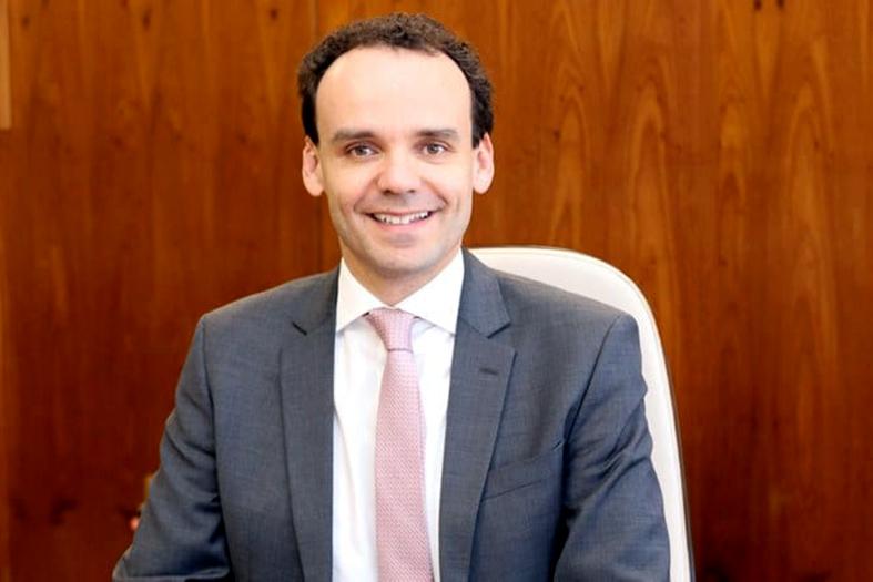 Procurador da República, Edilson Vitorelli, homem de pele branca e cabelos na cor preta. Ele veste um terno na cor cinza claro e uma gravata rosa.