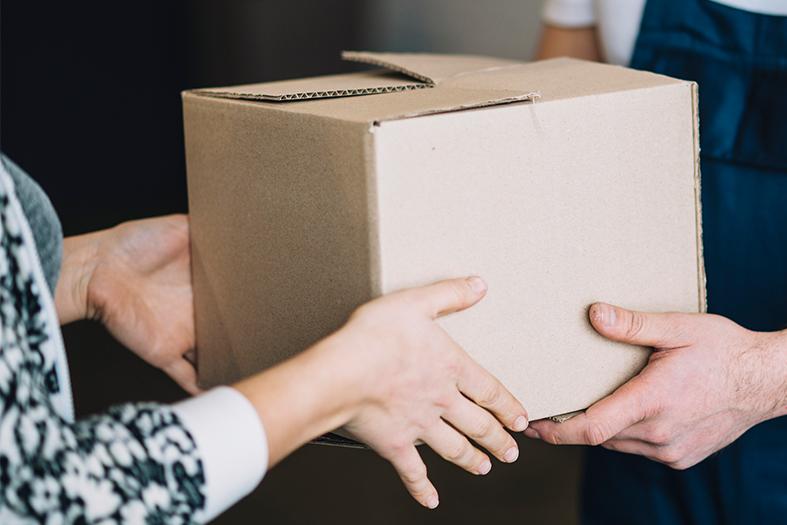 Detalhe das mãos de uma mulher recebendo uma caixa de papelão das mãos de um entregador.