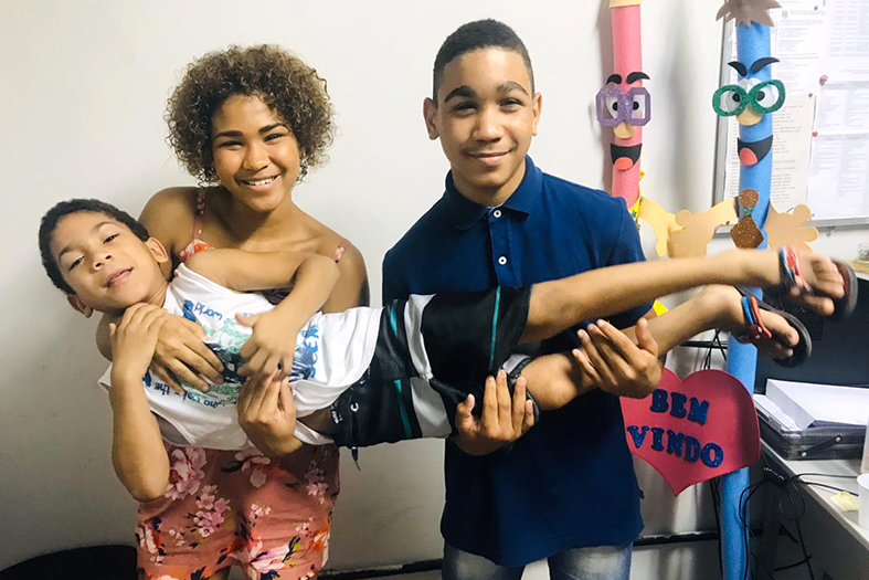 duas crianças, uma menina e um menino, carregam juntos em seus braços uma terceira criança. Ao fundo objeto lúdicos e brinquedos.