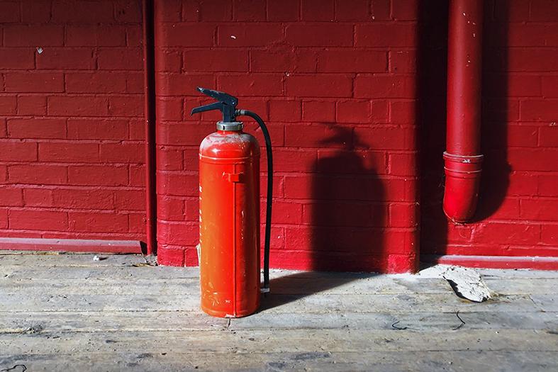 Um extintor de incêndio repousa sobre o chão de cimento.