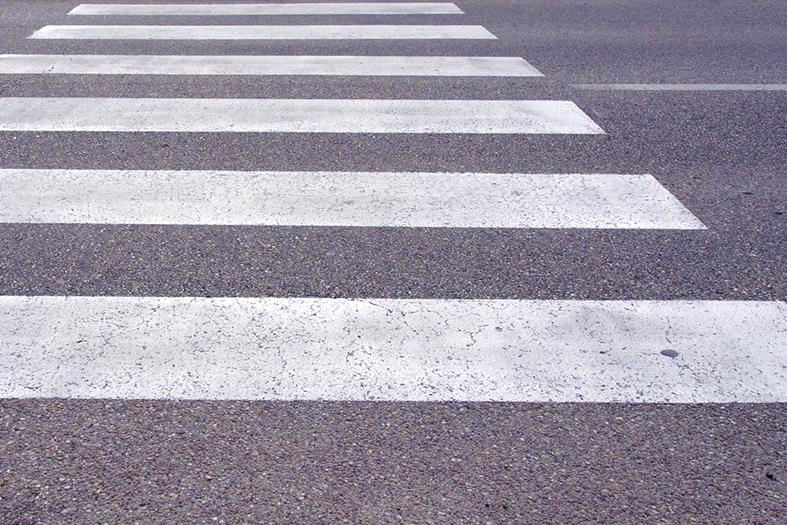 Asfalto pintado com faixa de pedestres na cor branca.