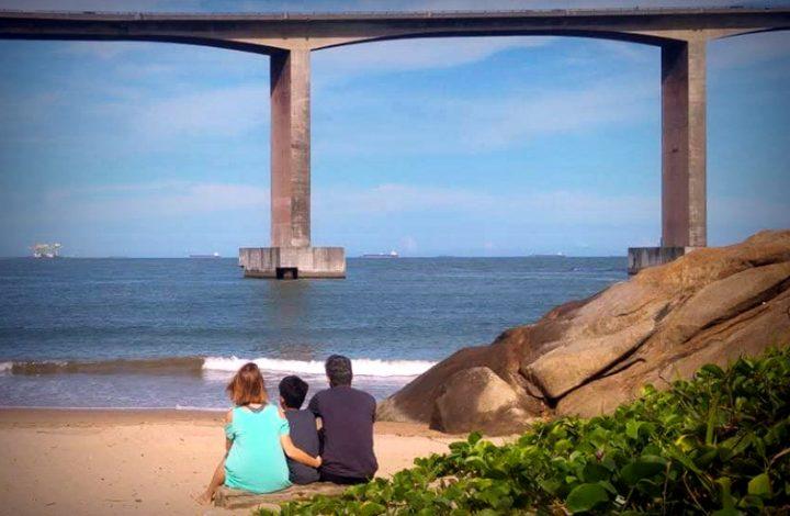 Pessoas de costas admirando a enseada do suá e a vista da terceira ponte.