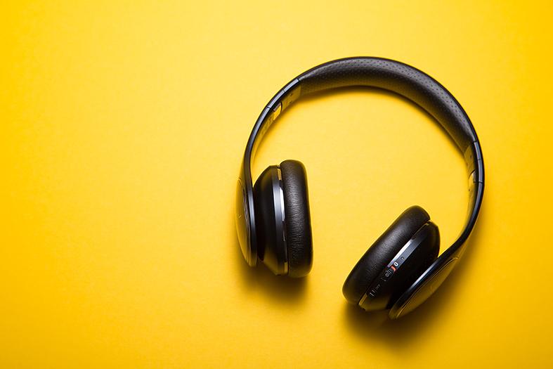 Fone de ouvido grande de cor preta sob fundo amarelo.