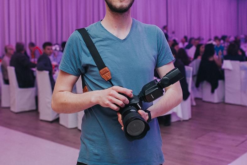 Homem carregando uma máquina fotográfica em suas mãos, ao fundo um salão arrumado com a predominância da cor lilás.