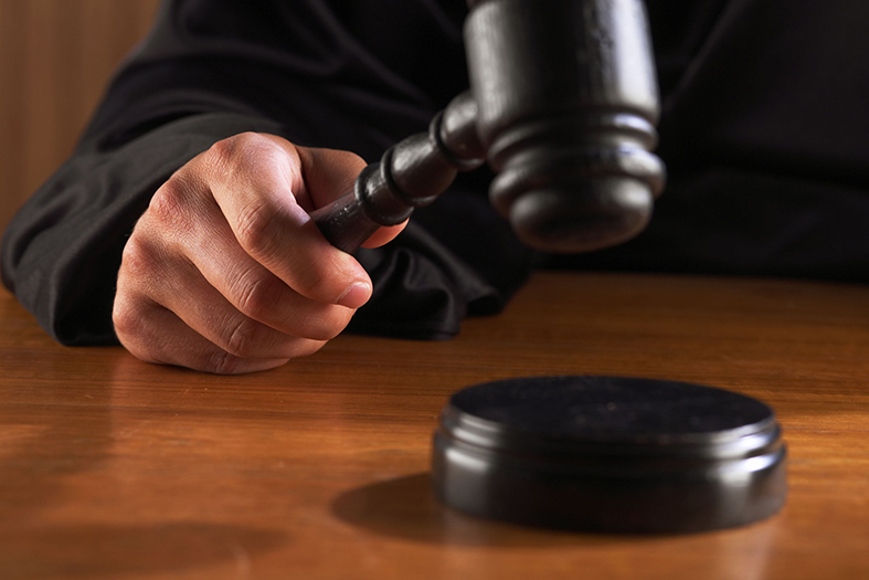 detalhe de um magistrado batendo com o gavel na base de madeira