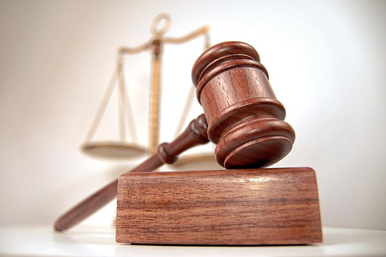 Em primeiro plano: gavel e base para batê-lo. Em plano de fundo: Balança, símbolo da justiça.