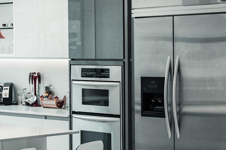geladeira de inox ao lado de um forno em uma cozinha em tons cinzas