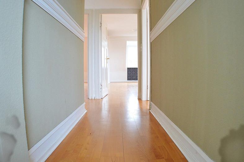Corredor interno de um apartameento onde se vê em primeiro plano que as paredes de cor creme estão com manchas de infiltração próxima ao rodapé de cor branca.