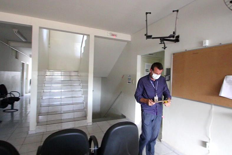 Homem de roupa social e usando máscara cirúrgica caminha por um corredor com cadeiras de espera.