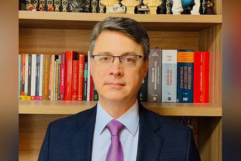 Juiz Carlos Magno Moulin Lima, homem de pele branca e de cabelos grisalhos. Ele usa óculos de armação fina e terno na cor azul escuro.