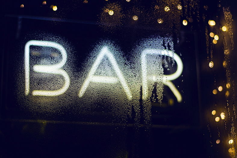 """Letreiro em neon com a palavra """"bar"""" em maiúsculas."""
