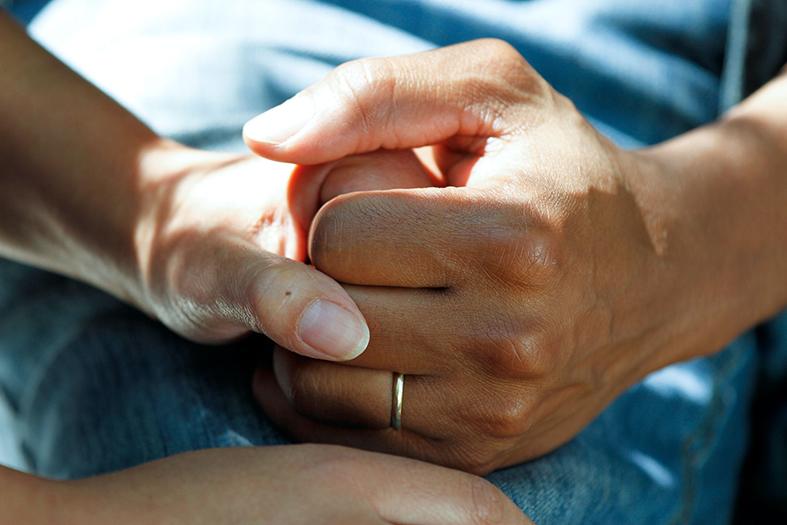 detalhe de uma pessoa segurando na mão de uma outra demonstrando cuidado, apoio.