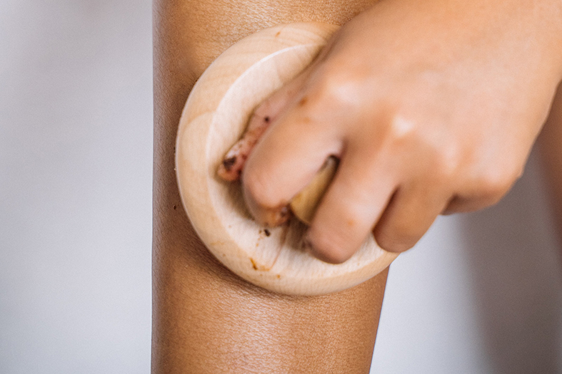 detalhe da mão de uma mulher usando um massageador em sua perna