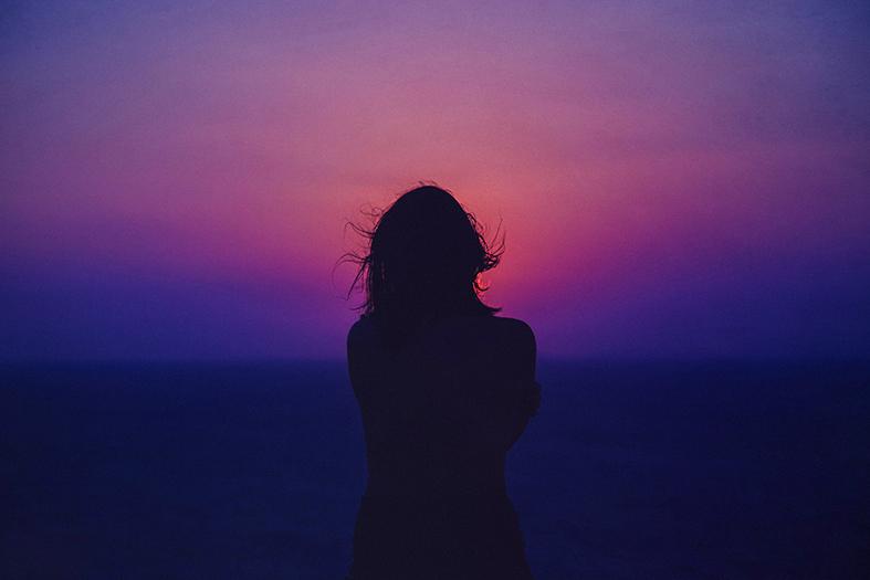 silhueta de uma mulher contrastando com um pôr do sol púrpura.
