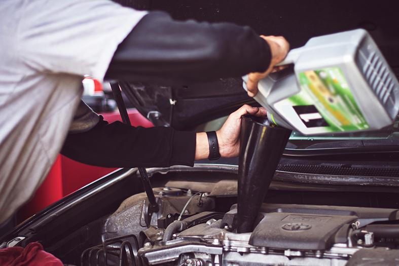 Funcionário troca óleo do motor de um carro.