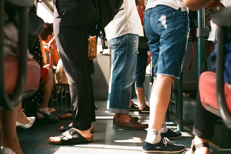 Visão das pernas de passageiros viajando em um ônibus.