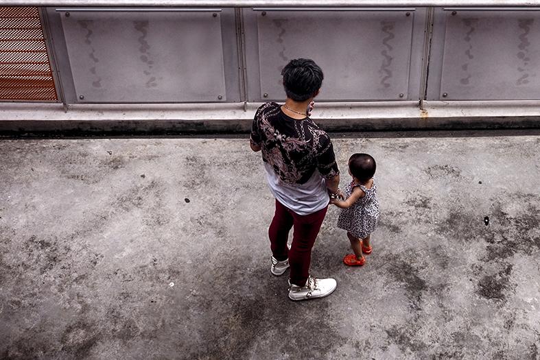Pai e filho pequeno parados em um pátio cujo piso de cimento está manchado de preto.