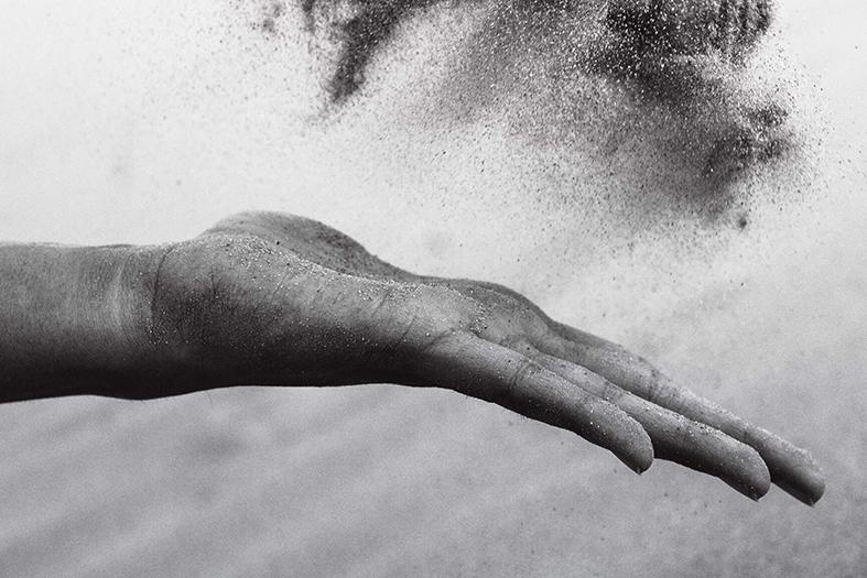 Foto preto e branco de uma mão jogando poeira ao ar.