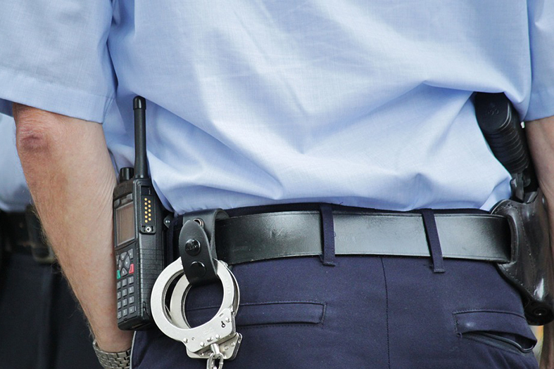Um policial de costas com uma algema pendurada no cinto e uma arma