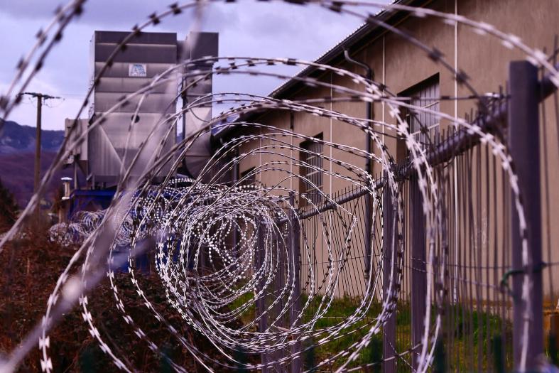 Arame de concertina enrolado protegendo o topo de um muro de prisão. ao fundo uma guarita.
