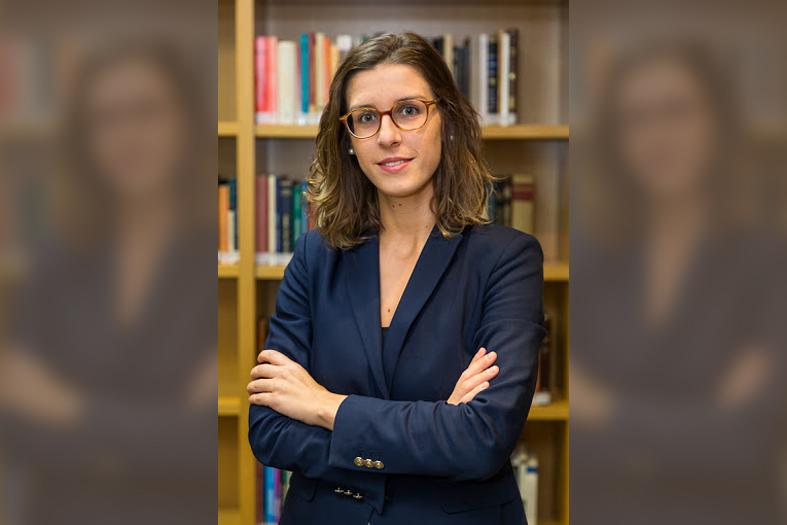 professora sofia temer posa para foto trajando um terno do tipo tailleur na cor azul escuro. Ao fundo uma estante de livros.