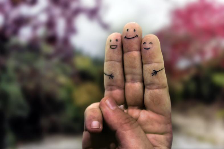 mão com três dedos levantados e nos dedos foram desenhado olhos e bocas dando a impressão de estarem se abraçado e felizes.