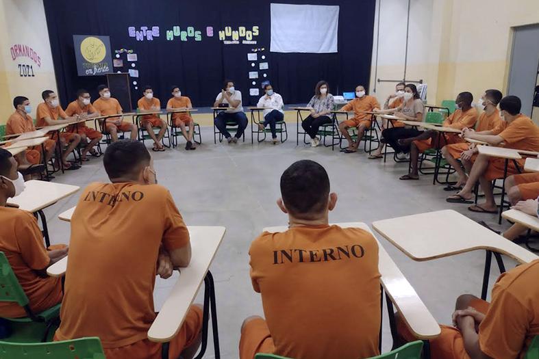grupo de reeducandos do sistema prisional sentados em cadeiras formando um círculo assiste a uma