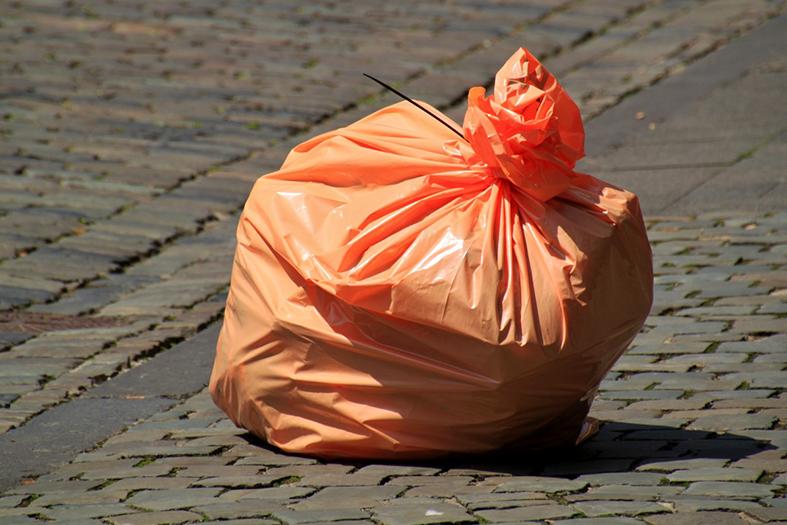 Saco de lixo na cor laranja deixado sozinho em calçada.