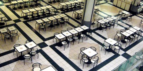 Salão vasto com inúmeras mesas com quatro cadeiras cada sugerindo uma praça de alimentação típica de shoppings.