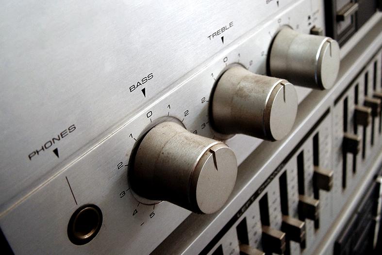 Detalhe de controles de áudio de um som estéreo.