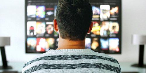 Homem assiste a tv.