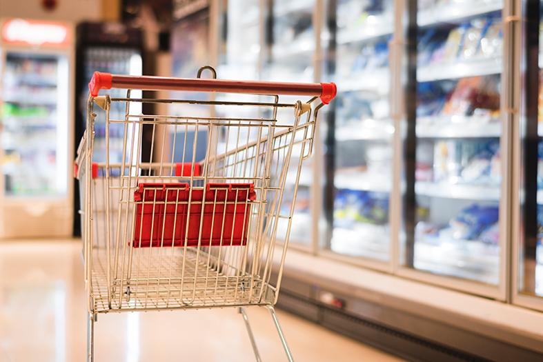 Seção de frios/congelados de um supermercado onde vemos um carrinho vazio.