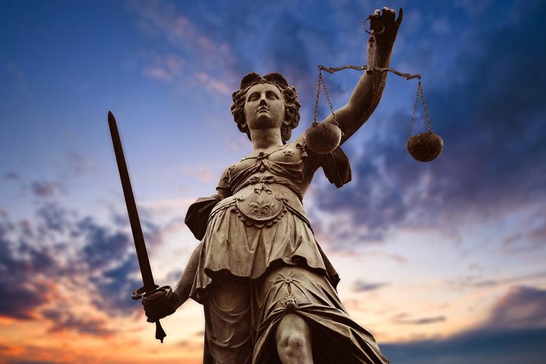 deusa Themis que representa a justiça. Ao fundo da estátua um céu em tons amarelados e cheio de nuvens.