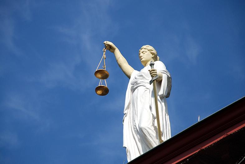 estátua da deusa themis vista de um ângulo de baixo para cima. a estátua é branca, ela segura uma balança dourada. a estátua está posta em cima de uma estrutura alta.