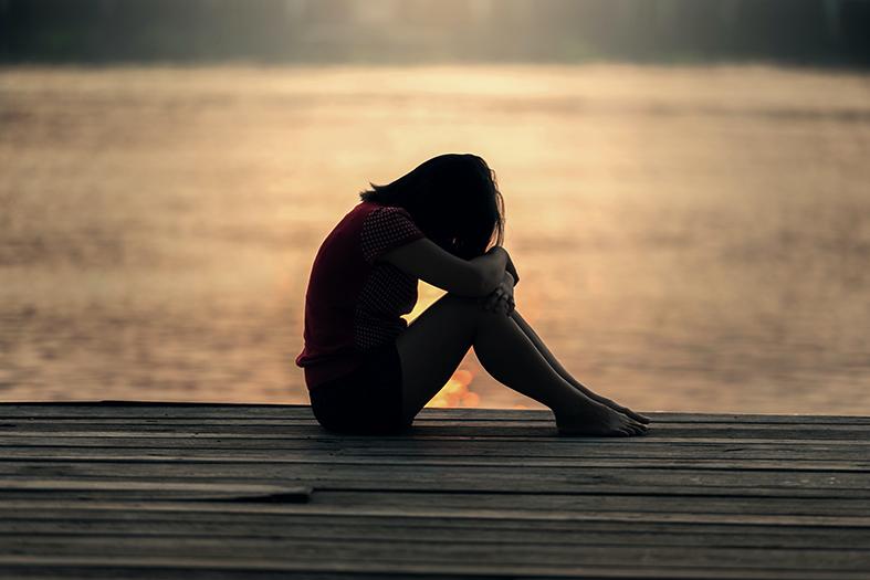 mulher jovem sentada em posição encolhida, com a cabeça e os braços encostados nos joelhos. Ela está sentada em uma deck de madeira.