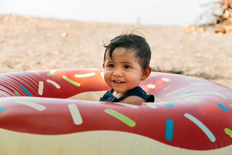 Em uma praia, criança de colo brinca dentro de uma boia decorada como uma rosquinha.