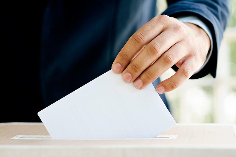 mão masculina coloca papel branco em uma urna de papelão. A pessoa veste terno azul marinho.
